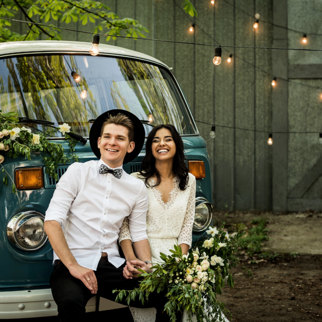 Boho Couple posing with camper van after their wedding ceremony